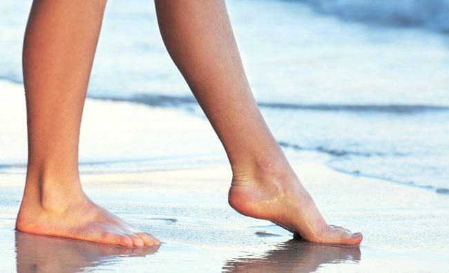 zadbane kobiece stopy bez żylaków na plaży