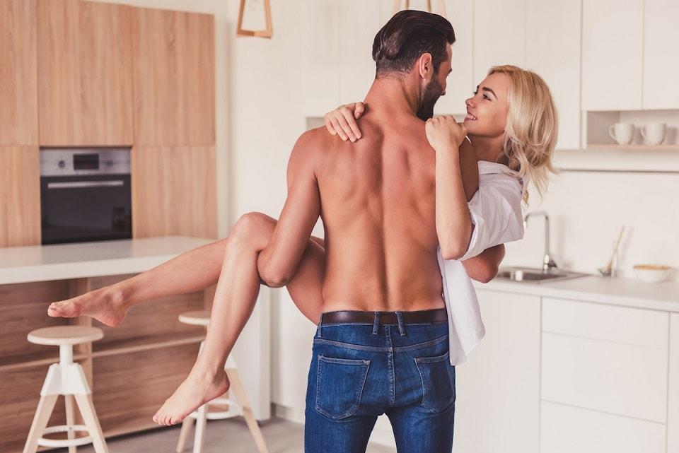 mężczyzna trzyma kobietę na rękach