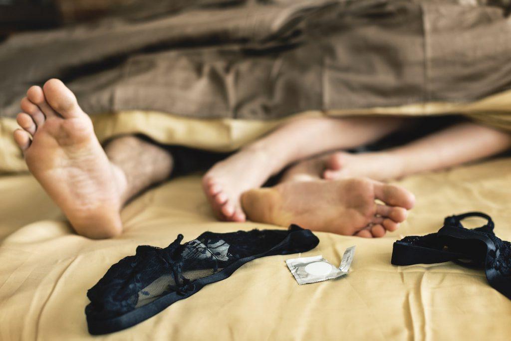 stopy młodych osób w łóżku