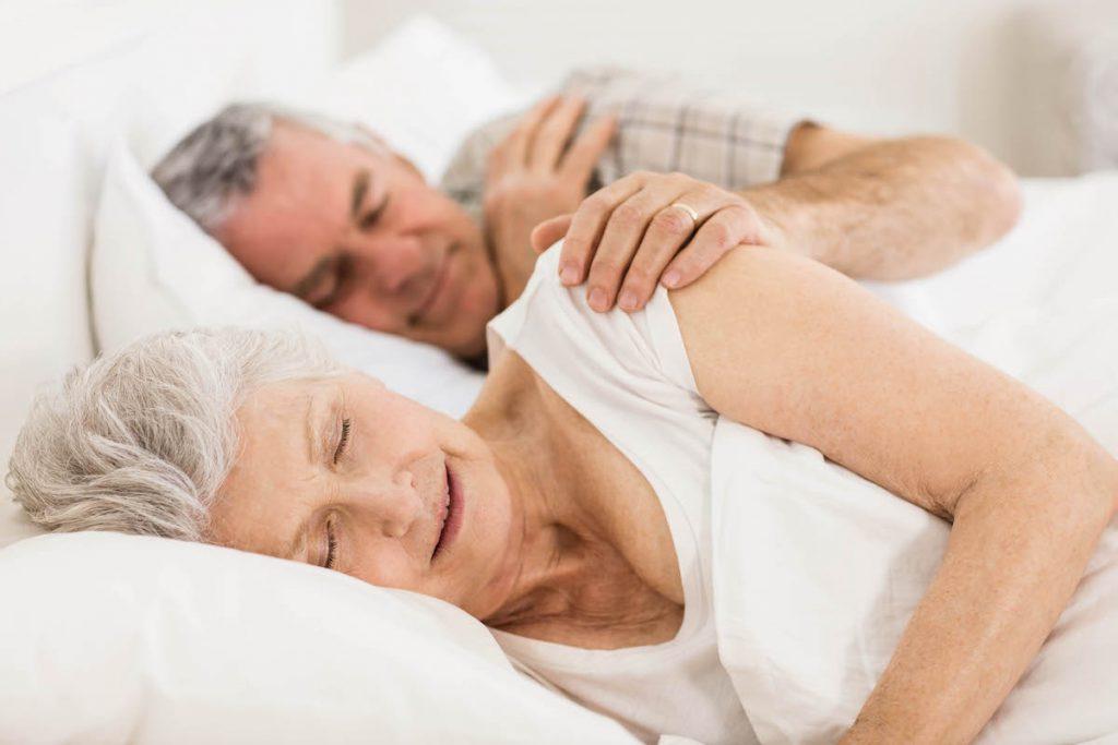 starsze małżeństswo śpi w łóżku w domu