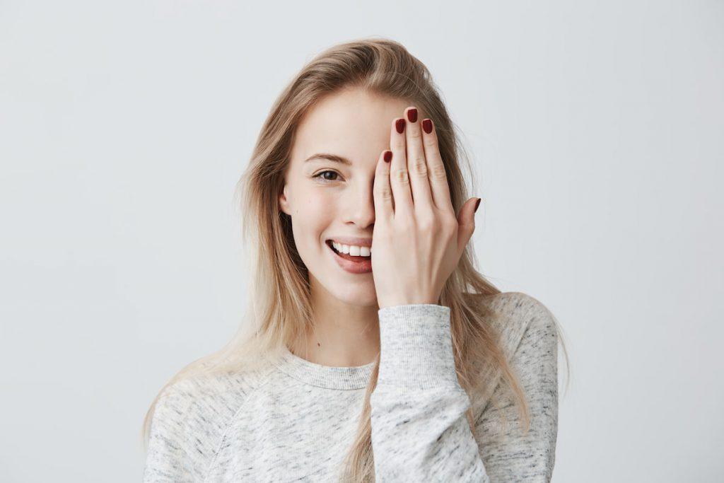 kobieta zasłaniająca oko